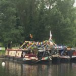 Barges and rowing boats moored on river and decorated with bunting ready for the festival