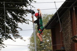Photograph of student scaling the ropes